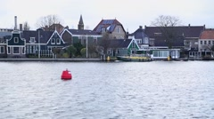 Boats sails next to the traditional Dutch village Stock Footage