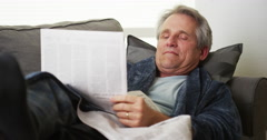 Senior falls asleep reading newspaper Stock Footage