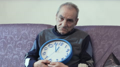 Old man with a wall clock: time passing, time left, end of life Stock Footage