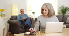 Senior adults using electronic devices at home - stock footage