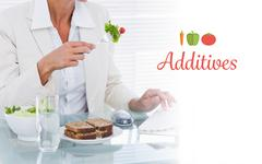Additives against businesswoman using computer while eating salad at desk - stock photo