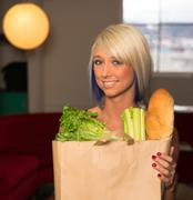 Attractive Female Homemaker Sets Grocery Bag on Counter Stock Photos
