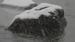 Stone Cold River | heavy snowfall on river rocks Stock Footage