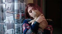 Young woman playing with a red tabby kitten Stock Footage