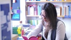 Woman reading in the bookshop Stock Footage