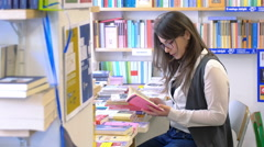 young student reading a book in the bookshop - stock footage