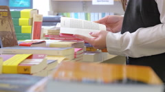 young woman reading a book near bookshelf in a bookshop - stock footage