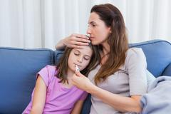 Mother taking temperature of sick daughter Stock Photos