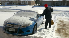 4K Man cleaning off snow from car in driveway Stock Footage