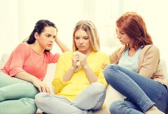 two teenage girls comforting another after breakup - stock photo