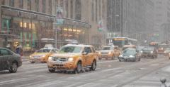 Snowing in New York City street car traffic yellow cabs Stock Footage
