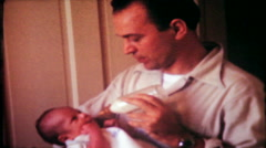 1775 - father bottle feeds his baby boy at home - vintage film home movie - stock footage
