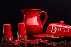 Red salt-cellar, pepper-box, butter and pitcher set on darck background - stock photo