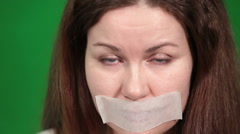 Voiceless Caucasian woman with tape on mouth blinking eyes, close up face view Stock Footage