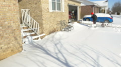 4K man clearing snow from front porch / sidewalk of home Stock Footage