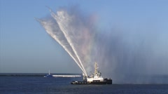 Tugboat Brent performs a water salute by spraying water in the air Stock Footage