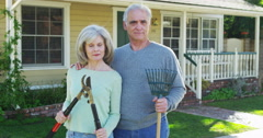 Senior couple holding gardening tools outdoors Stock Footage