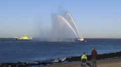 Spectators on quay, fireboat performs a water salute - long shot Stock Footage