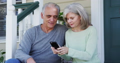 Senior couple using social media on smartphone Stock Footage