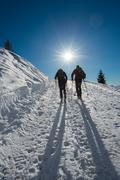 Couple of ski mountaineering at the sun - stock photo
