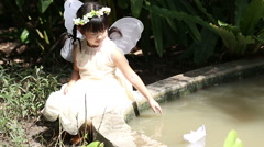 Little asian girl floating paper boat with smiling face in the park Stock Footage