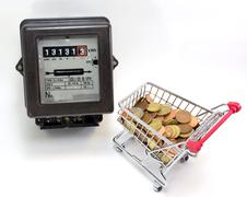 shopping cart full of European currencies and the electricity meter - stock photo