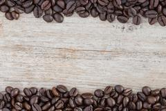 Stock Photo of close up coffee beans on wood background space for sample text