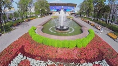 People walk by Pushkinskaya square with flowerbed and fountain Stock Footage