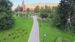 Stock Video Footage of Tourists walk by alley of Aleksandrovsky garden near Kremlin wall