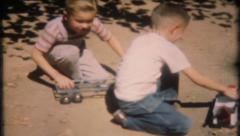 1780 - boys play with toy trucks in the backyard dirt - vintage film home movie Stock Footage