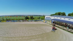 Tractor smooths sand on equestrian arena Sozidatel Stock Footage