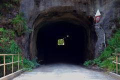 dark tunnel in a mountain on a road - stock photo
