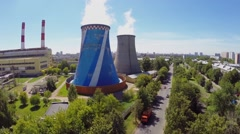 Cars ride by street near power plant at summer sunny day Stock Footage