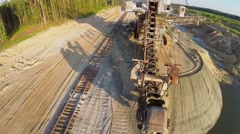 Big absetzer and railroad at sandpit near forest during sunset Stock Footage