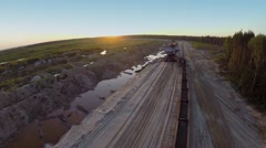 Absetzer loads train at sandpit during sunset. Aerial view Stock Footage