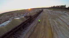 Worker in helmet and uniform walks near train Stock Footage