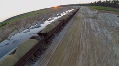 Train carries sand in open wagons at sandpit in summer Stock Footage