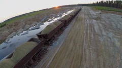 Train with sand in open wagons rides by sandpit at summer Stock Footage