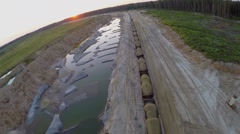 Train with sand rides by sandpit near forest at summer evening Stock Footage