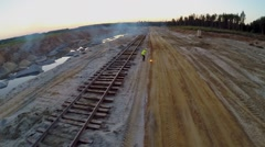 Woman in helmet and uniform put out signal fire near railway Stock Footage