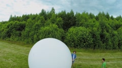 People set up white sphere at stick on field in Wonderland Park Stock Footage
