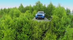 Mini cooper among leaves on trees near field with people Stock Footage