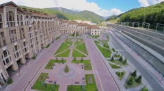 Cars ride by quay in mountain town near river and railroad Stock Footage