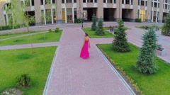Woman in pink dress walks by paved square near hotel Stock Footage
