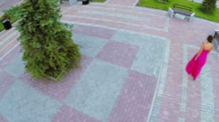 Woman in pink dress walks by paved square and sits on bench Stock Footage