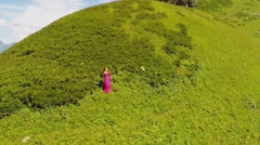 Woman in pink dress stands on slope of mountain Black Pyramid Stock Footage
