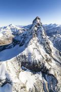 The unique shape of the Matterhorn sorrounded by its mountain range covered in - stock photo
