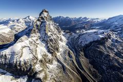 The massive shape of the Matterhorn sorrounded by its mountain range covered in Stock Photos