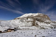 The mountain hut at the foot of Plattkofel (Sasso Piatto) under a starry winter - stock photo