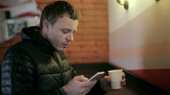 Man drinking coffee and using smartphone Stock Footage